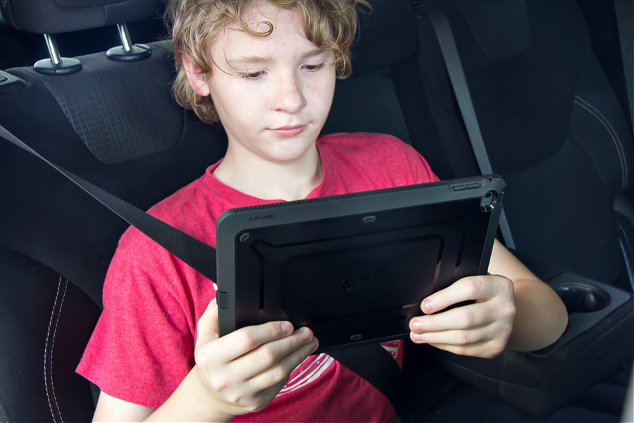 A boy in a car holding an iPad for a long road trip.