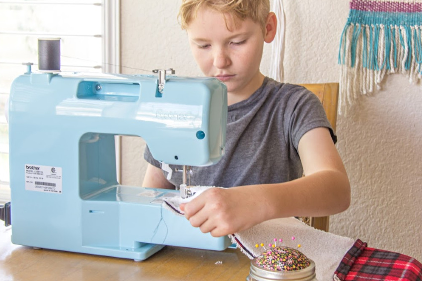 A boy learning to sew his own fleece book pillow