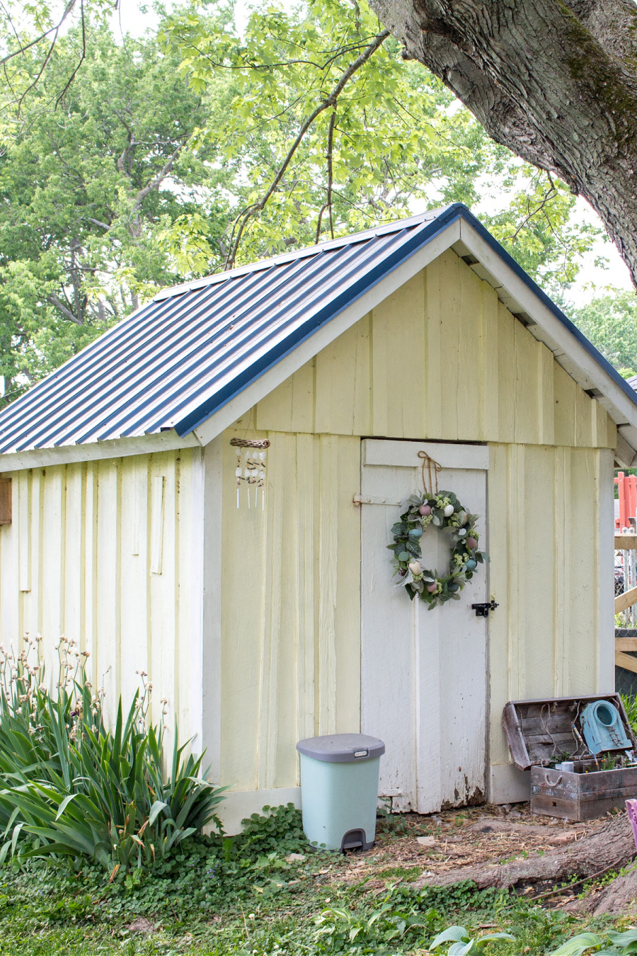 A yellow garden shed with wood door converted into a chicken coop.