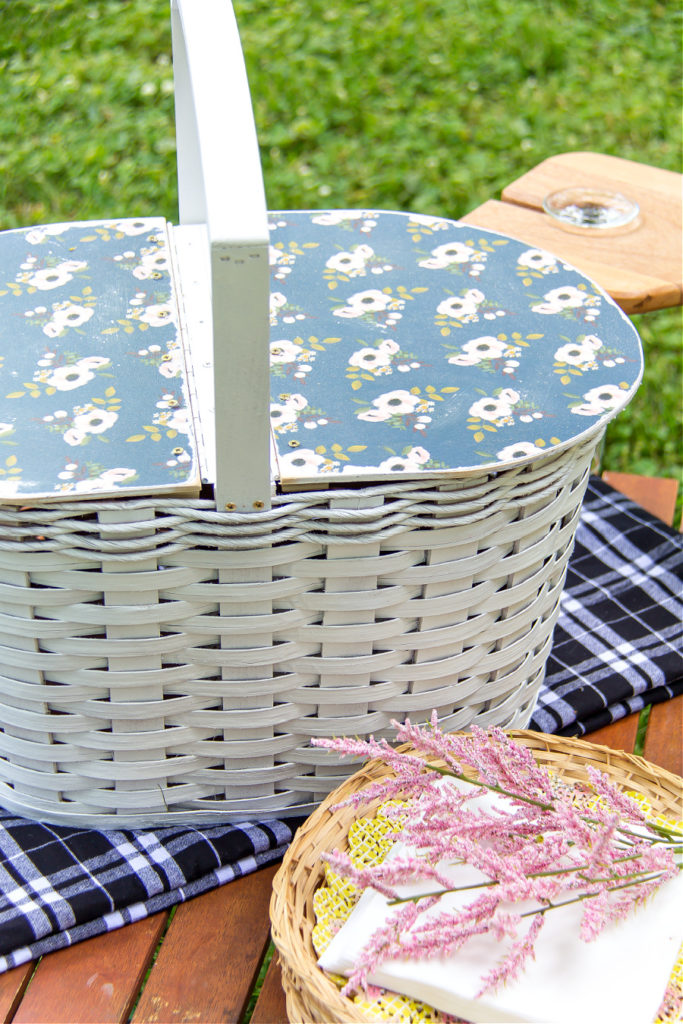 A DIY white picnic basket with a Mod Podge blue flower wood lid on top.