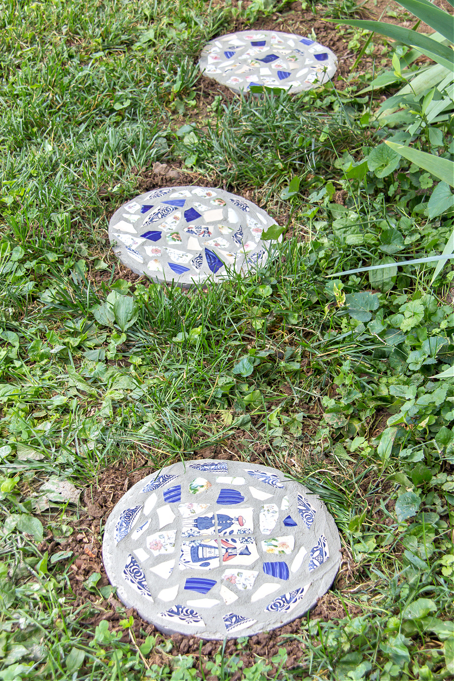 Round concrete stepping stones made with fast setting concrete and broken plates.