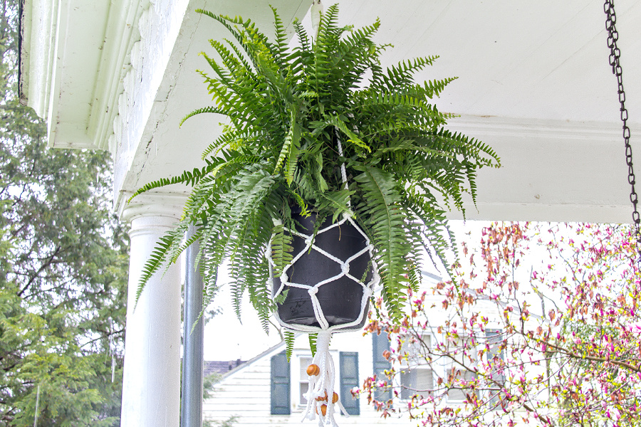 A white weatherproof macrame plant hanger for front porch ferns.