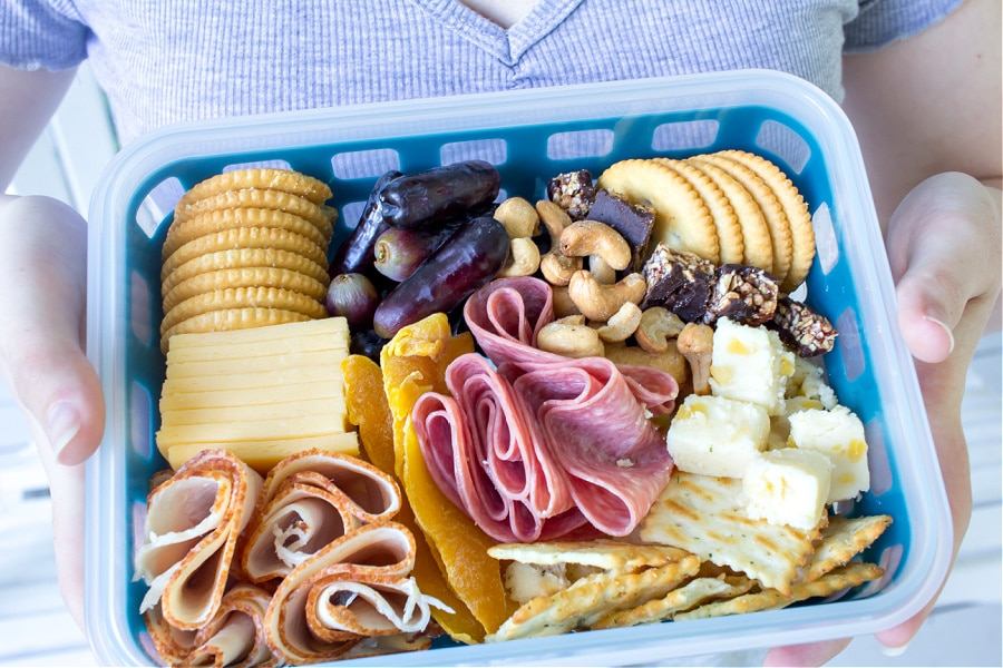 A charcuterie inspired lunch box for teenagers including meats, cheese, fruit, and nuts.
