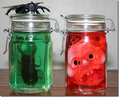 Jars with colored liquid, bugs and shrunken heads to make Halloween specimen jars for Halloween decorating.