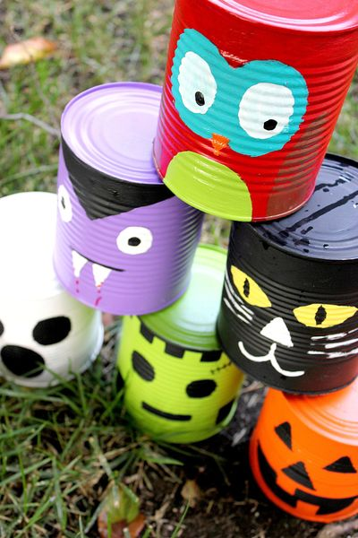 Halloween kids craft tin can toss game. Tin cans are painted like skeletons, jack o lanterns, Frankenstein, and more.