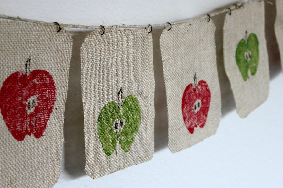 A burlap banner stamped with painted apples.