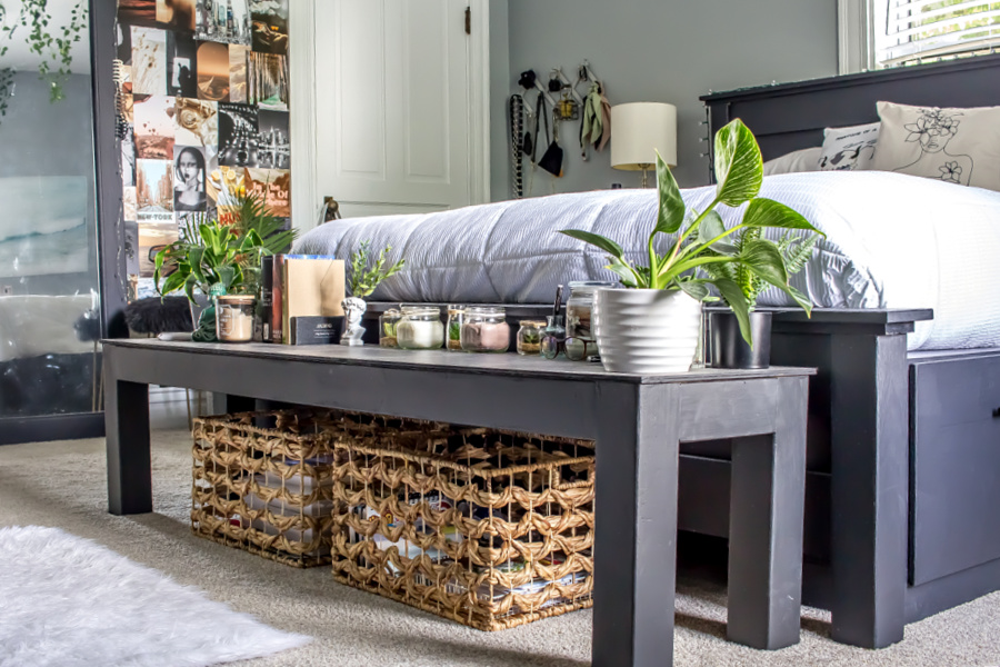 A black end of bed bench with baskets underneath and candles and plants on top.
