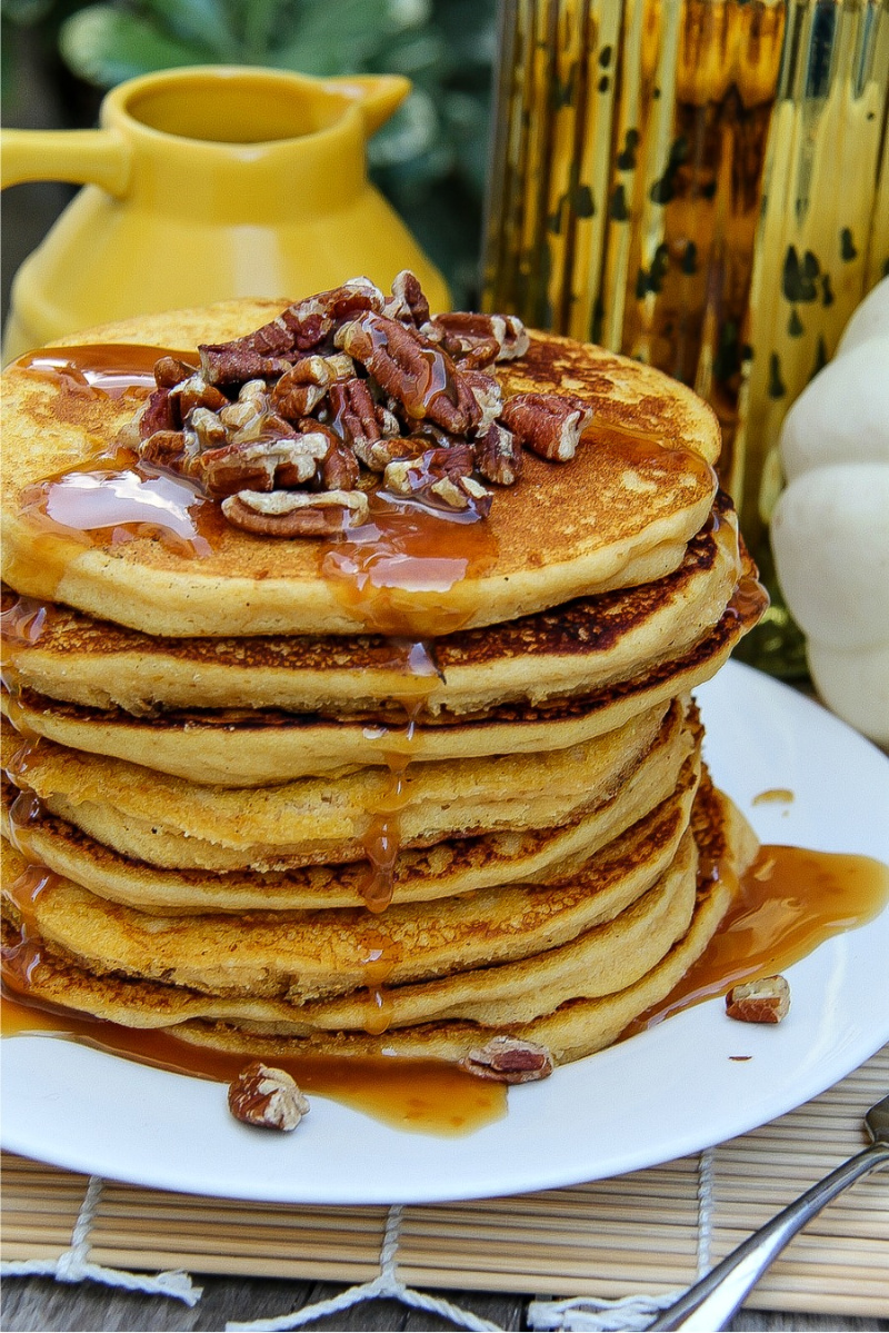 Gluten-free pumpkin pancakes with maple syrup and pecans.