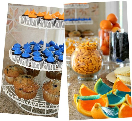 orange and blue party food including cupcakes, jelly orange slices, goldfish, fruit, and muffins.